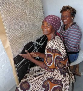 Gertrude and Lisabeth at hand loom weaving a rug